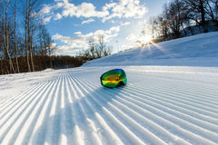 Unbroken ski slope and goggles. Unbroken ski slope, goggles and cloudy sky Stock Image