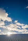 Unbroken ski slope, sun and blue sky. Unbroken ski slope, sun and blue cloudy sky Royalty Free Stock Image