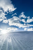 Unbroken ski slope, sun and blue sky. Unbroken ski slope, sun and blue cloudy sky Stock Images