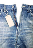 Unbuttoned blue jeans with paper label Stock Image