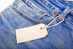 Unbuttoned blue jeans with paper label Stock Images