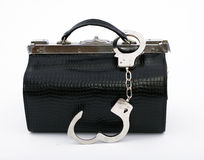 Unbuttoned handcuffs pinned to black leather bag Stock Photo