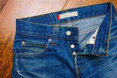 Unbuttoned jeans. Indigo jeans on the shelf in the store. Unbuttoned jeans, close-up Royalty Free Stock Photo