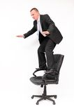 Uncertain business. Businessman standing on a chair trying to keep his balance Stock Photo