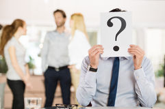 Uncertain business future. Businessman holding a question mark sign in front of his face. Confused businessman explaining his state of mind about his career Royalty Free Stock Photography