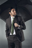 Uncertain businessman with umbrella Royalty Free Stock Image