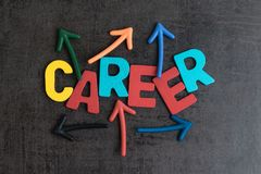 Uncertain career path opportunities concept by colorful wooden a. Lphabets CAREER with multi directional arrow on dark black cement wall stock image