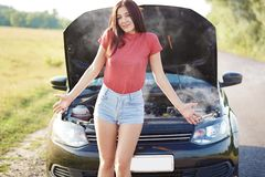 Uncertain European woman shruggs shoulders, dressed in summer clothes, doesnt know how to solve problem with brocken car, poses. Outside on road, waits for royalty free stock photo