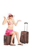 Uncertain female tourist sitting on her baggage Royalty Free Stock Images