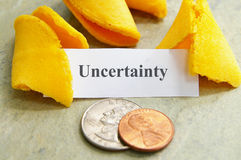 Uncertain future. Fortune cookie and coins with Uncertainty text Stock Images