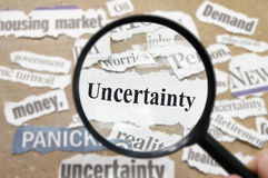 Uncertain future. News headlines and magnifying glass with Uncertainty text Royalty Free Stock Images