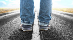 Uncertain future. Close up of feet of man on long straight asphalt road Stock Photos