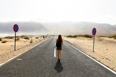 Uncertain future. Young alone woman advances with an uncertain step in empty asphalt desert road. Apocalypse concept.  Stock Photos