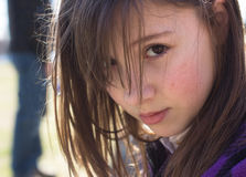 Uncertain Girl. A girl looking uncertain while off in the distance a figure lurks behind her royalty free stock photography