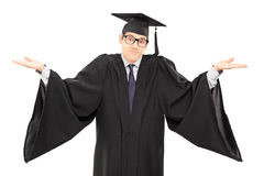 Uncertain student in graduation gown gesturing with hands. Isolated on white background Royalty Free Stock Image