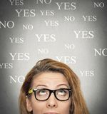 Uncertain woman looking up, background with yes no choices. Portrait undecided uncertain woman looking up, grey wall background with yes no choices text. Human Royalty Free Stock Images