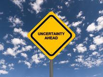 Uncertainty ahead. Yellow road side style sign on a post with text 'uncertainty ahead' in black uppercase letters, blue sky and cloud background Stock Images