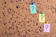 uncertainty or doubt concept, question mark on a sticky note on cork bulletin board stock photography