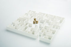 The uncertainty of money and business. Coins stack hidden inside a maze Stock Images