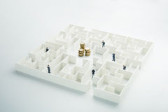 The uncertainty of money and business. Coins stack hidden inside a maze Stock Photos