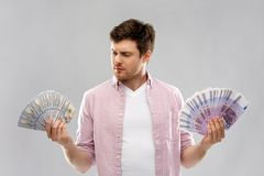 Uncertainy man with fans of euro and dollar money. Money, finance, business and exchange rate concept - uncertain young man with hundreds of euro and dollar bank stock photos