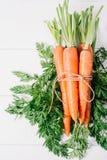 Unch di giovani carote con le cime verdi sulla tavola d'annata di legno bianca, alimento sano su derisione sulla vista superiore  fotografie stock