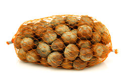 Unch of fresh hazelnuts in a plastic net. Bunch of fresh hazelnuts in a plastic net on a white background Royalty Free Stock Image