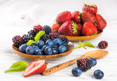 Вunch of wild berries and mint. On a wooden board Stock Photos