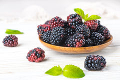 Вunch of wild berries and mint. On a wooden board Stock Photography