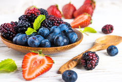 Вunch of wild berries and mint. On a wooden board Royalty Free Stock Photography