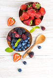 Вunch of wild berries and mint. On a wooden board Stock Photo
