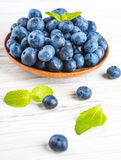 Вunch of wild berries. And mint on a wooden board Stock Photo