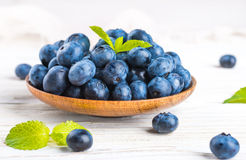 Вunch of wild berries. And mint on a wooden board Royalty Free Stock Image