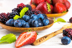 Вunch of wild berries. And mint on a wooden board Royalty Free Stock Photo