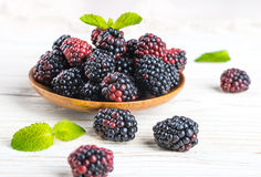 Вunch of wild berries and mint. On a wooden board Royalty Free Stock Image