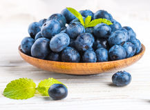 Вunch of wild berries and mint. On a wooden board Royalty Free Stock Photos