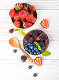 Вunch of wild berries and mint. On a wooden board Royalty Free Stock Photo