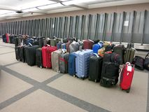 Unclaimed Luggage at Baggage Claim. Unclaimed luggage piles up at an airport baggage claim after no one claims it, much of which is due to late or delayed Royalty Free Stock Photo
