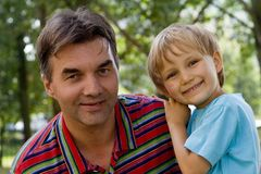 Uncle And Nephew. Portrait of smiling uncle and young nephew.  Nephew is leaning on the shoulder of his uncle.  Taken outdoors Stock Images