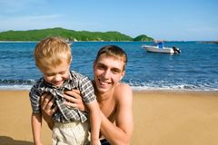 Uncle & nephew. The uncle and the nephew on a sea beach. In the sea there is a yacht Stock Photography