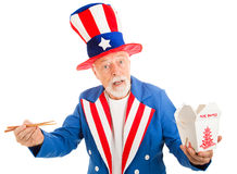 Uncle Sam Eats Chinese. American icon Uncle Sam tries to figure out how to eat Chinese food with chopsticks. Isoalted on white stock photography