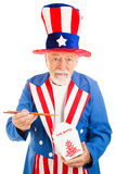Uncle Sam Eats Chinese Takeout. American icon Uncle Sam eating Chinese takeout food with chop sticks. Metaphor for US debt to China or poor eating habits royalty free stock photo