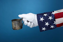 Uncle Sam goes panhandling. Uncle Sam with cup in hand looks for money royalty free stock photos