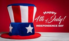 Uncle Sam Hut auf rotem Hintergrund mit glücklichem am 4. Juli grüßen Stockbilder