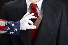 Uncle Sam picks businessman's pocket. Close up shot of Uncle Sam picking the pocket of a businessman stock image