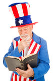 Uncle Sam Reads the Bible. American icon Uncle Sam reading the Bible. Isolated on white stock photography