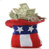Uncle Sam's Money Hat. Closeup of an Uncle Sam hat overflowing with US dollar bills. On a white background royalty free stock photo
