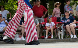 Uncle Sam Strides Past. Spectators watch the 2011 July 4th Parade in Amherst, New Hampshire, as Uncle Sam on stilts walks past stock photography