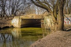 Unclean river. An old abandoned bridge over a small impure river Stock Photo