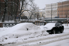 Uncleaned Street in Saint-Petersburg. SAINT-PETERSBURG, RUSSIA - JANUARY 7: Cars under snow in St.Petersburg on the day of the Russian Christmas January 7, 2010 Royalty Free Stock Photo